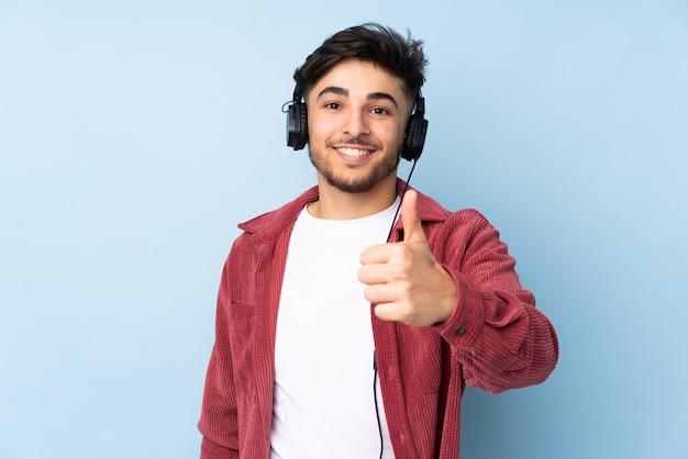 Arabski przystojny mężczyzna na niebieską ścianą słuchania muzyki i kciukiem do góry