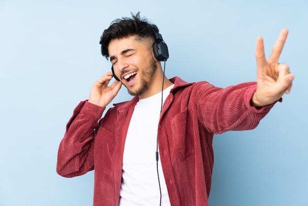 Arabski przystojny mężczyzna na niebieską ścianą słuchania muzyki i śpiewu