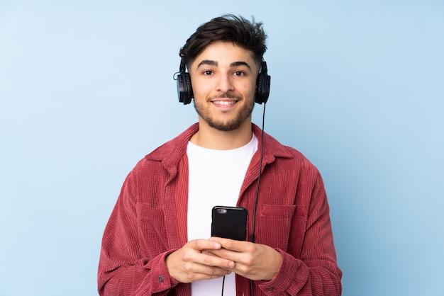 Arabski przystojny mężczyzna na niebieską ścianą słuchania muzyki z telefonu komórkowego i patrząc z przodu