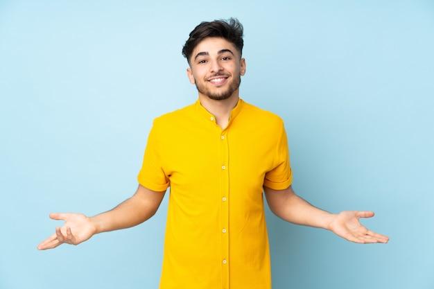 Arabski przystojny mężczyzna na odizolowanej ścianie szczęśliwy i uśmiechnięty