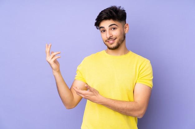 Arabski przystojny mężczyzna na odizolowanej ścianie wyciągając ręce na bok, by zaprosić do przyjścia