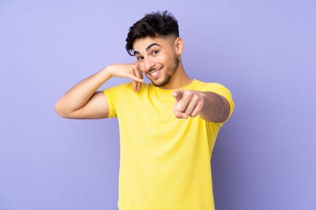 Arabski przystojny mężczyzna nad ścianą robi telefonicznemu gestowi i wskazuje przód