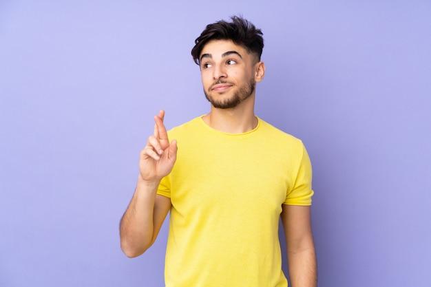 Arabski przystojny mężczyzna nad ścianą ze skrzyżowanymi palcami i życzący jak najlepiej