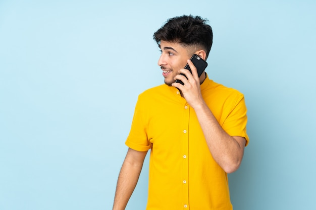 Arabski przystojny mężczyzna przez ścianę prowadzący z kimś rozmowę z telefonem komórkowym