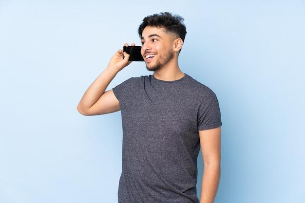 Arabski przystojny mężczyzna przez ścianę prowadzenie rozmowy z telefonem komórkowym