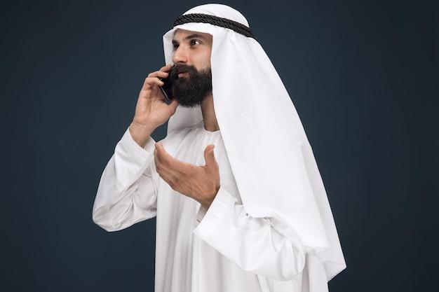 Arabski saudyjski mężczyzna na ciemnym niebieskim tle studio