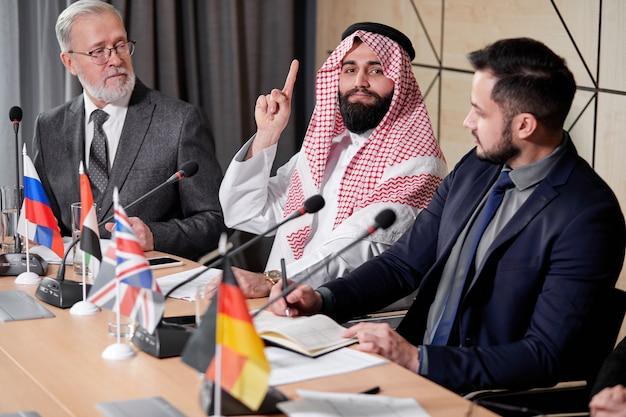 Arabski szejk organizuje spotkanie bez powiązań, aby omówić pomysły i problemy z porządku obrad, używając mikrofonu do wygłaszania przemówień. w sali posiedzeń zgromadzili się razem wieloetniczni koledzy