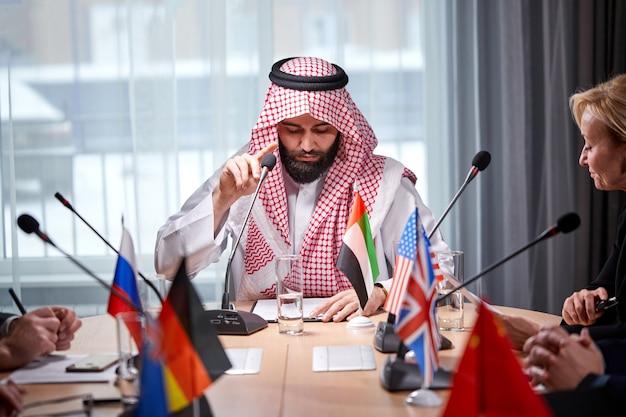 Arabski szejk przedstawia swoje pomysły różnym wieloetnicznym kolegom i nasłuchuje pomysłów na inwestycje w jasne, nowoczesne biuro, używa mikrofonu. spotkanie bez krawatów