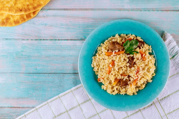 Arabskie danie z ryżem, mięsem, marchewką i chlebem pita