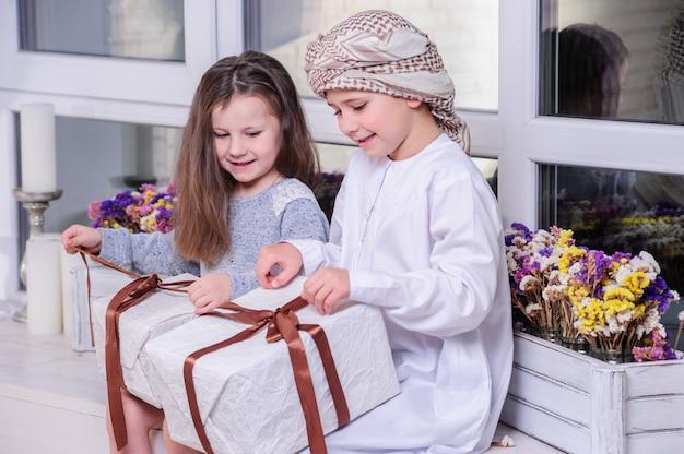 Arabskie dzieci rozpakowują prezent.