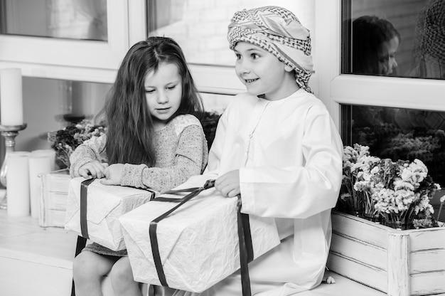 Arabskie dzieci rozpakowujące prezent.