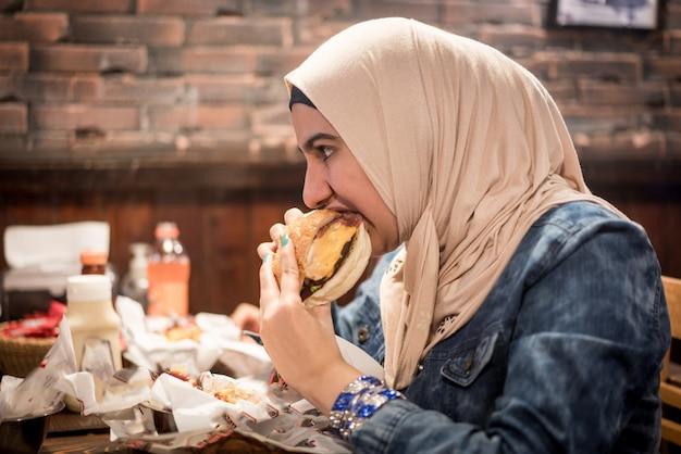 Arabskie dziewczyny w restauracji fast food, jedzenie hamburgera