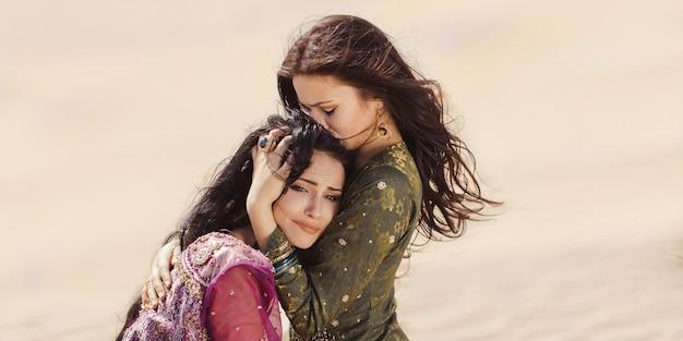 Arabskie dziewczyny zagubione w wydmach podczas podróży.