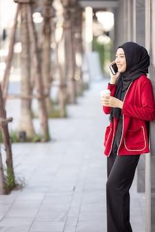 Arabskie kobiety biznesu w hidżabie, trzymając kawę na ulicy i trzymając telefon komórkowy
