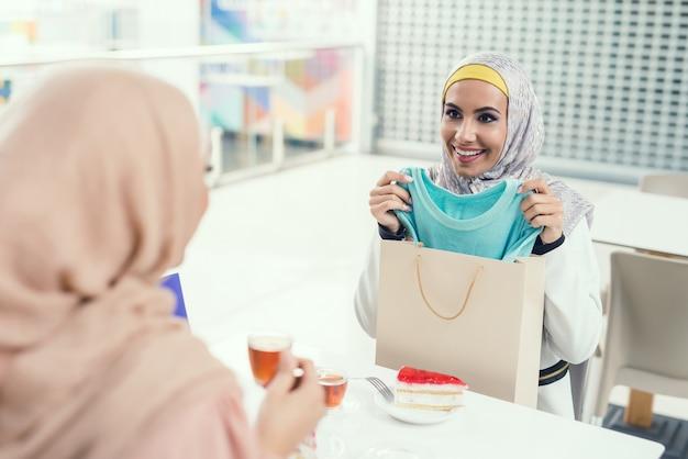 Arabskie kobiety siedzą w kawiarni w nowoczesnym centrum handlowym.