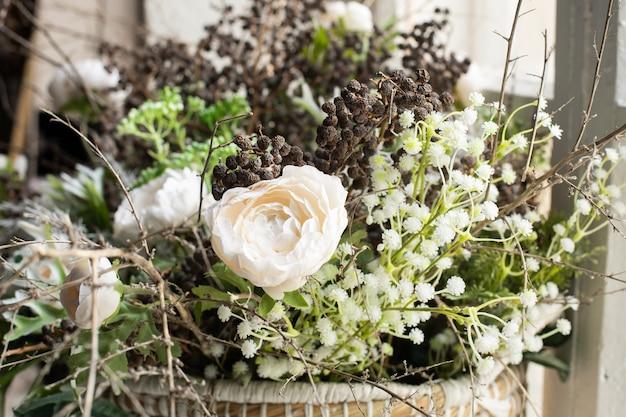 Aranżacja białych kwiatów i suszonych kwiatów w wiklinowym koszu