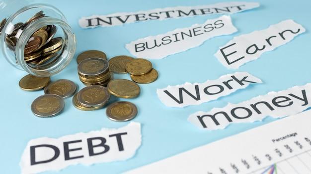 Aranżacja elementów ekonomicznych z monetami i słowem zapisanym na kartkach papieru