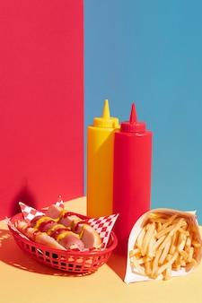 Aranżacja jedzenia z hot dogiem i butelką musztardy