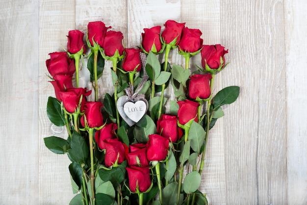 Aranżacja róż w kształcie serca, drewniane serduszka na drewnianym tle
