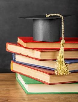Aranżacja różnych książek z czapką dyplomową