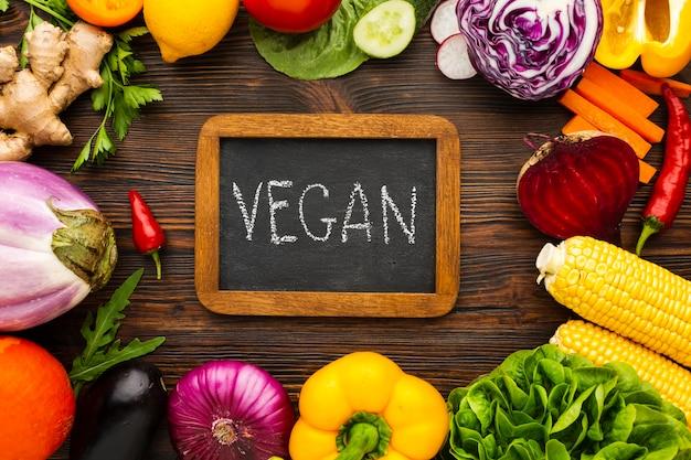 Aranżacja warzyw z napisem wegańskim na tablicy