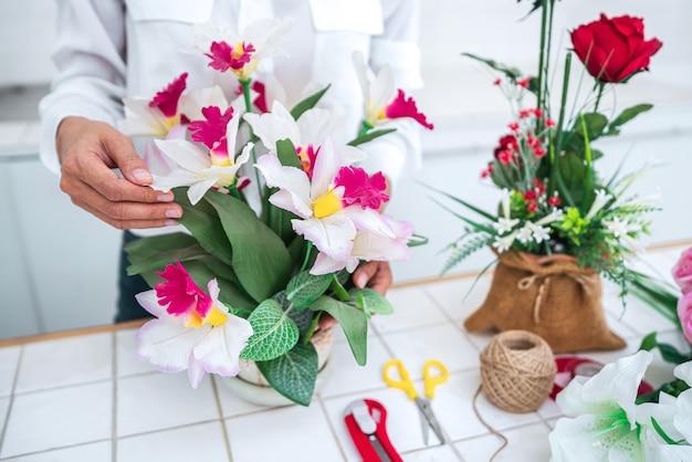 Aranżowanie sztucznych kwiatów, młoda kobieta kwiaciarnia organizuje sztuczne kwiaty