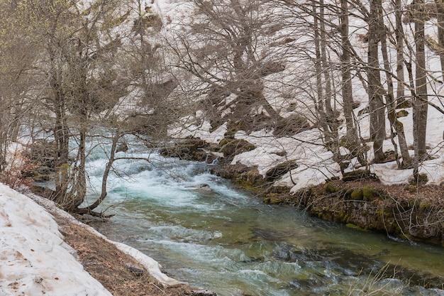 Arazas rzeka w ordesa y monte perdido parku narodowym z śniegiem.