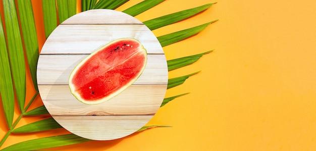 Arbuz na drewnie na liściach tropikalnych palm