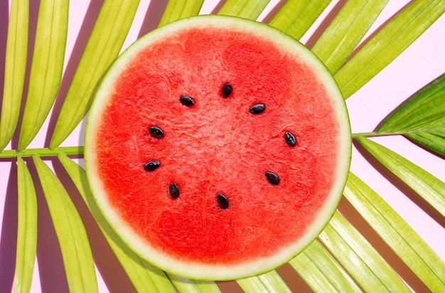 Arbuz na tropikalnych liściach palmowych na różowej powierzchni