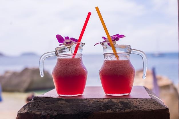 Arbuz smoothie w szkle z arbuzem i kwiatem na plaży
