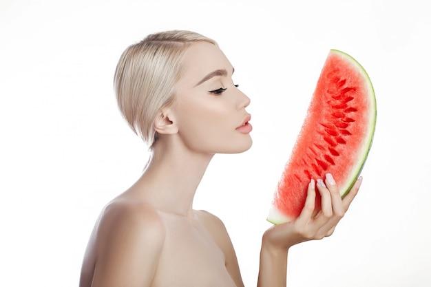 Arbuz w rękach kobiety, czysta gładka skóra ciała i twarzy. blondynki dziewczyna trzyma arbuza w rękach twarz w lecie. zabieg przeciwzmarszczkowy i przeciwstarzeniowy, naturalne kosmetyki przeciwstarzeniowe