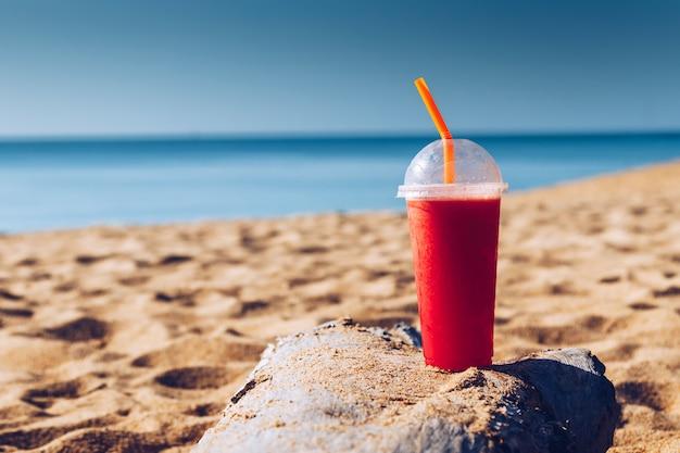 Arbuza sok z słomą w szkle na piasek plaży przy phuket tajlandia. koncepcja lato