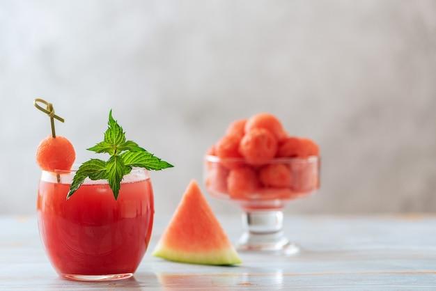 Arbuzowy napój w szklanych i arbuzowych kulkach. orzeźwiający letni koktajl.