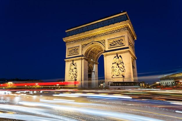 Arc de triomphe nocą ze światłami samochodowymi