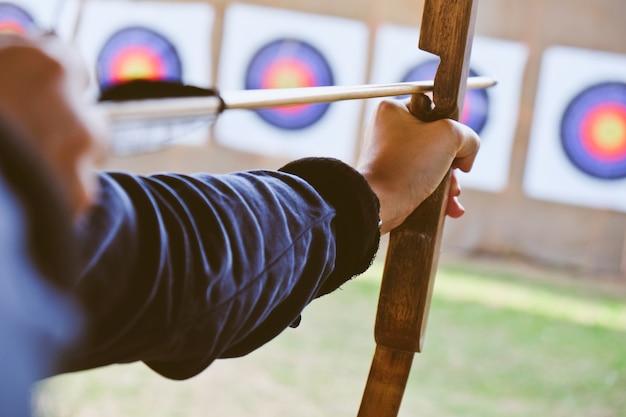Archer trzyma swój łuk, celując w cel