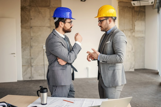 Architekci dyskutują o swoim projekcie stojąc w budynku w trakcie budowy
