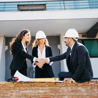 Architekci noszący hełmy, ściskając dłonie