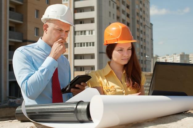 Architekci pracują przed budynkiem