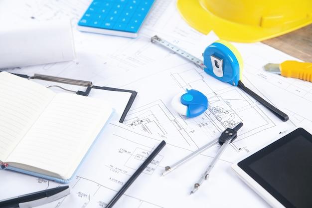 Architekci pracują z taśmą mierniczą, planem projektu architektonicznego i innymi obiektami.