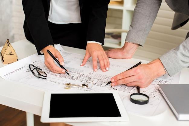 Architekci studiujący plan z makietą