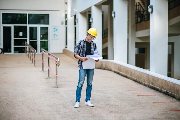 Architekci trzymają plan budynku i sprawdzają prace.