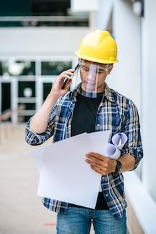 Architekci trzymają plany pięter i rozmawiają przez telefon.