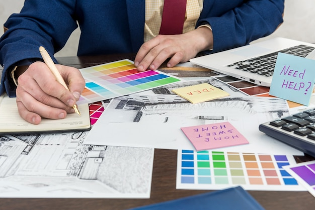 Architekci wykonują rysunek nowoczesnych apartamentów z próbką kolorów i laptopem na kreatywnym biurku, biurze. mężczyzna wybiera kolory do dekoracji pokoju