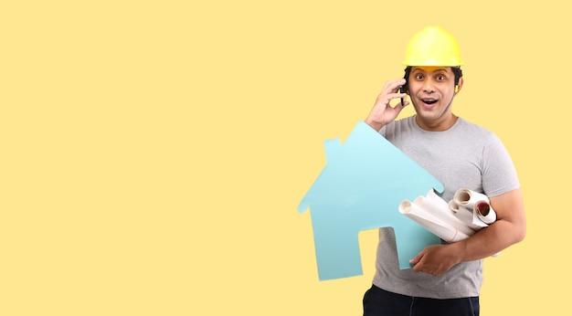 Architekt azjata szok i niespodzianka trzymania papierowego kształtu domu prezentującego inteligentny telefon na białym tle na żółtej ścianie
