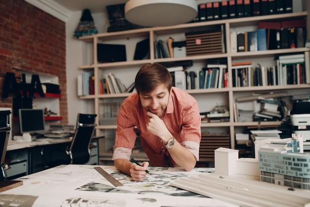 Architekt człowiek z planami i projektem roboczym układu w biurze architektonicznym
