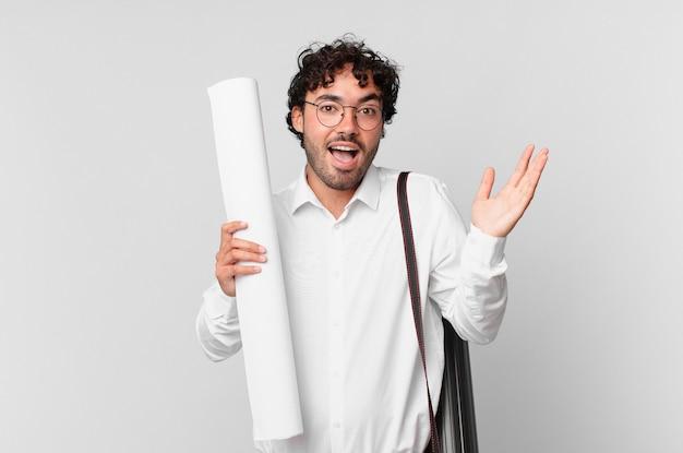 Architekt czujący się szczęśliwy, podekscytowany, zaskoczony lub zszokowany, uśmiechnięty i zdumiony czymś niewiarygodnym