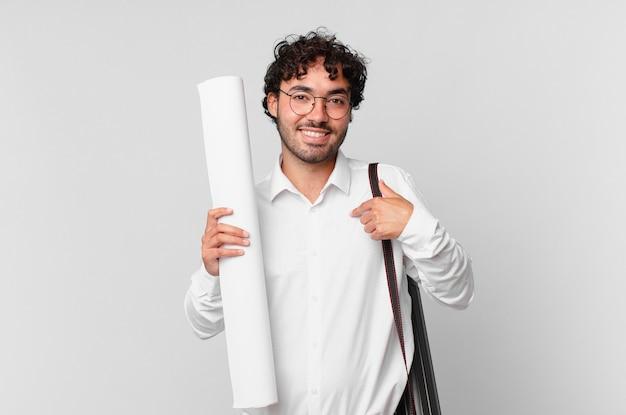 Architekt czujący się szczęśliwy, zaskoczony i dumny, wskazujący na siebie z podekscytowanym, zdumionym spojrzeniem