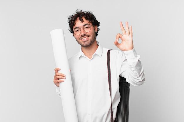 Architekt czujący się szczęśliwy, zrelaksowany i usatysfakcjonowany, okazujący aprobatę dobrym gestem, uśmiechnięty