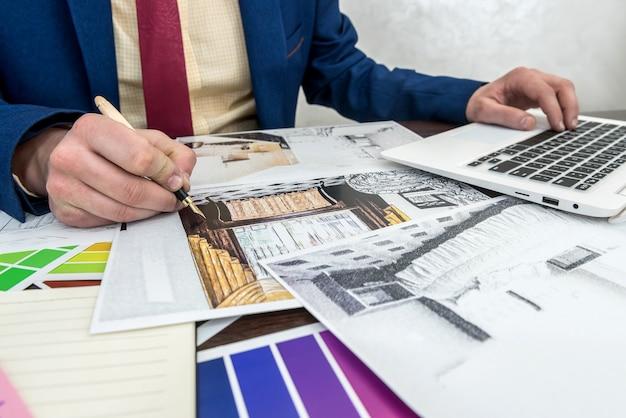 Architekt dobierający kolory do dekoracji wnętrz pokoju z laptopem i próbką kolorów. projektant wnętrz pracujący z paletą kolorów i szkicem domu