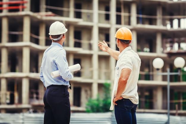 Architekt i budowniczy dyskutuje na budowie